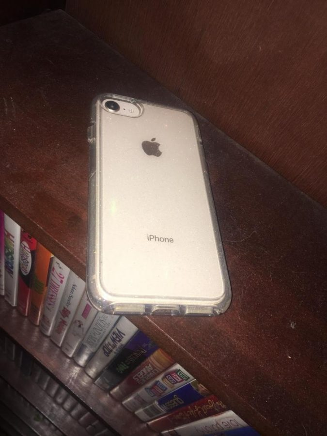 An iPhone 8 with a sparkle case laying on a shelf of movies. The phone has the gold finish and is the normal size. Photo taken by Nalia Nordman on October 4, 2017 at 10:33 P.M.
