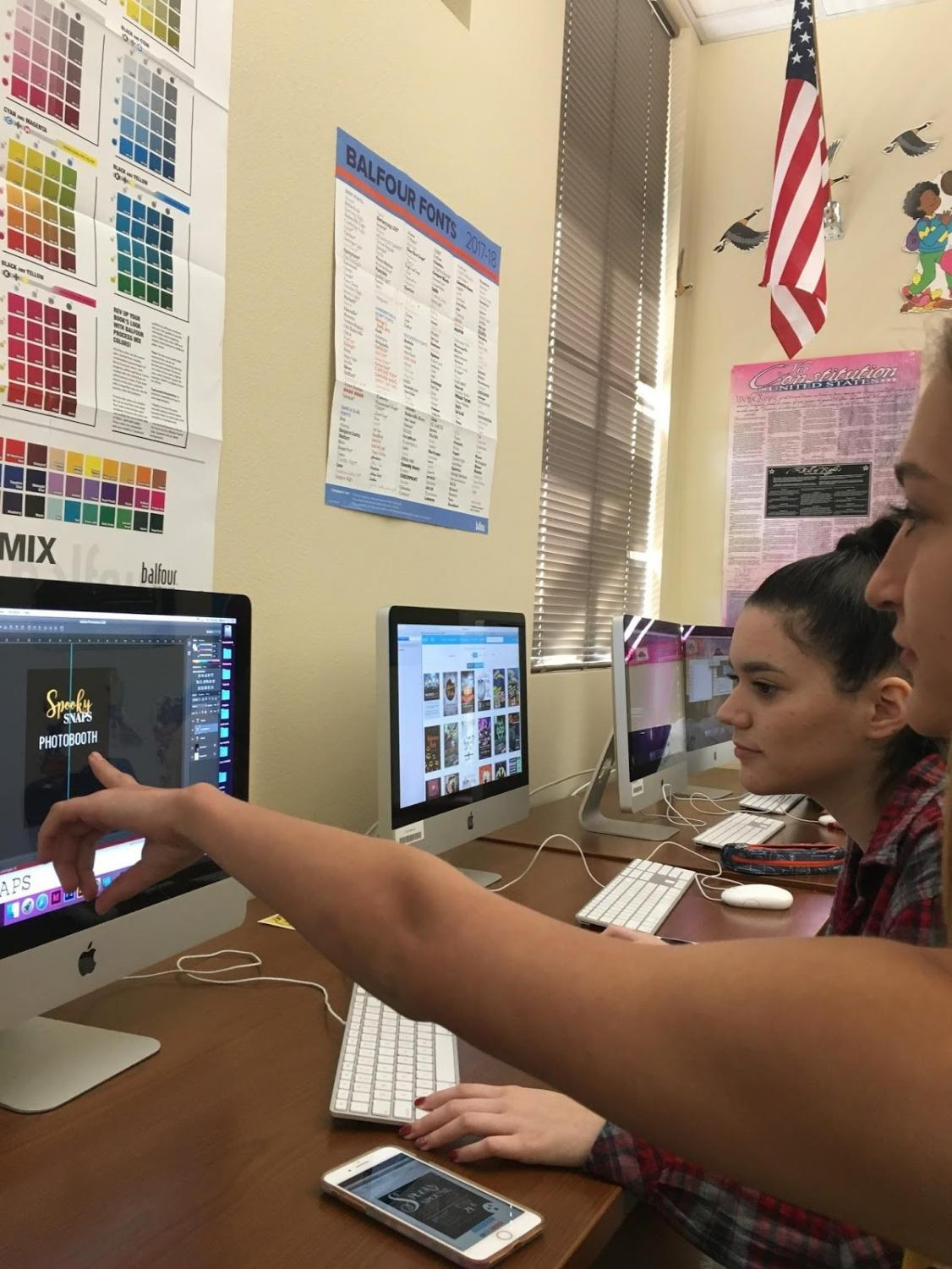 Yearbook members, Izabela Duarte and Nikki Nelson, work on making a flyer to advertise Spooky Snaps on October 19, 2017 in the yearbook classroom. The Spooky Snaps photo booth is an important fundraiser for raising money to improve the quality of this year's yearbook. Photo by Kayla Wilson.