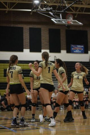 The varsity volleyball team celebrates scoring a point against Barry Goldwater High School at their home game on September 26, 2017. Their bond as a team has helped them to stay positive and strong as they play in tough conference games. Photo credit to Kayla Wilson.