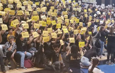 Students raise signs with junior Dylan Miller's jersey number, 11, at last week's assembly. Students were given the signs to show the family that they stand with Miller. Photo credit to Principal Kristen Tiffany.