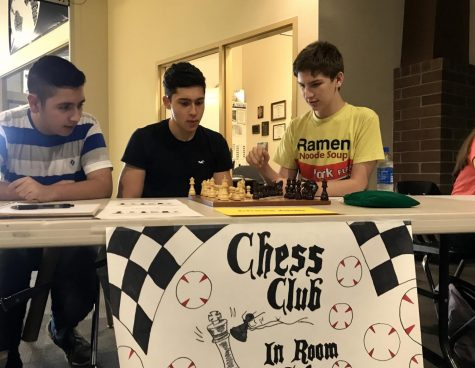 Chess Club members David Rincon (middle) and Todd Kleber (right) playing a game of chess to advertise their organization at Club Rush, August 27, as a fellow member Victor Ledezma watches (left). Photo by Camila Perdomo